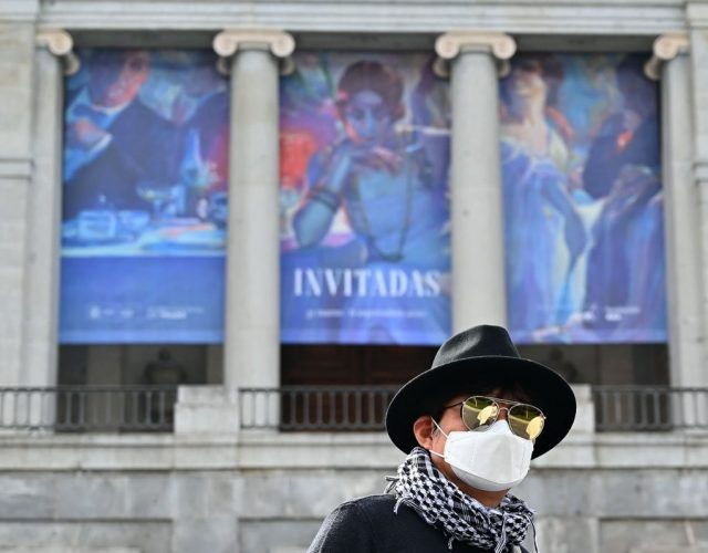 A South Korean tourists wearing a protective face mask walks in front of El Prado museum in Madrid on March 12, 2020, after all of Madrid's state-run museums were closed to the public due to the coronavirus outbreak. - Spain struggles to handle a quadrupling of cases in three days, taking the number of infections above 2,000 and 48 dead, with Madrid the worst-hit area accounting for more than half of the cases. (Photo by GABRIEL BOUYS / AFP) (Photo by GABRIEL BOUYS/AFP via Getty Images)
