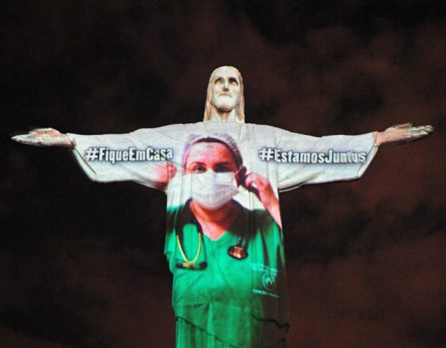 View of the world famous Christ the Redeemer statue on Easter day with a medical worker projected on it in honour of all the medical staff fighting the COVID-9 coronavirus pandemic worldwide in Rio de Janeiro, Brazil on April 12, 2020. (Photo by CARL DE SOUZA / AFP) (Photo by CARL DE SOUZA/AFP via Getty Images)