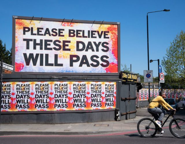 A cyclist rides past a billboard reading 'please believe these days will pass' in Shoreditch, east London, as the UK continues in lockdown to help curb the spread of the coronavirus. (Photo by Dominic Lipinski/PA Images via Getty Images)