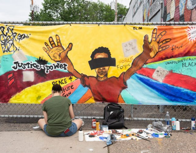 MINNEAPOLIS, USA - MAY 27: Destiny Randle works on a communal painting at the memorial site for George Floyd on Wednesday, May 27, 2020, during the second day of protests over his death. Floyd died in police custody in Minneapolis on Monday night, after an officer held his knee into Floyd's neck for more than 5 minutes. (Photo by Steel Brooks/Anadolu Agency via Getty Images)