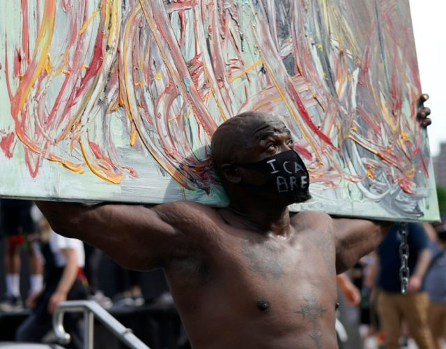 "A protestor carries a painting in search of justice for George Flyod, a black man who died after a white policeman kneeled on his neck for several minutes, on May 29, 2020, at Foley Square in New York during a ""Black Lives Matter"" protest. - Demonstrations are being held across the US after George Floyd died in police custody on May 25. (Photo by TIMOTHY A. CLARY / AFP) (Photo by TIMOTHY A. CLARY/AFP via Getty Images)"