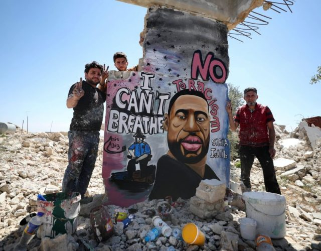 TOPSHOT - Syrian artists Aziz Asmar and Anis Hamdoun finish a mural depicting George Floyd, an unarmed African-American man who died while while being arrested and pinned to the ground by the knee of a Minneapolis police officer, in the town of Binnish in Syria's northwestern Idlib province on June 1, 2020. (Photo by OMAR HAJ KADOUR / AFP) (Photo by OMAR HAJ KADOUR/AFP via Getty Images)