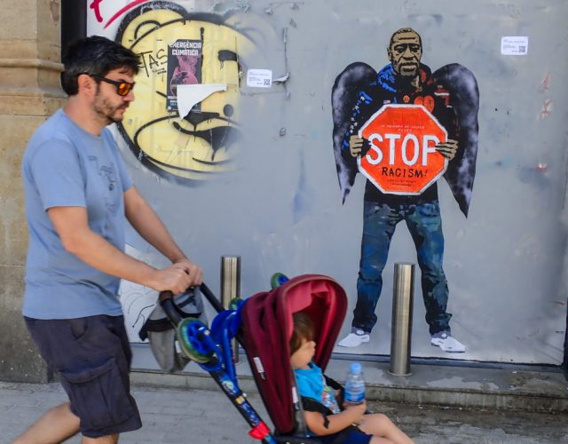"BARCELONA, SPAIN - MAY 31: A father pushes his son in a stroller past Graffiti in memory of George Floyd by Italian street artist TVBoy on May 31, 2020 in Barcelona, Spain. The death of an African-American man, George Floyd, at the hands of police in Minneapolis has sparked violent protests across the USA. A video of the incident, taken by a bystander and posted on social media, showed Floyd's neck being pinned to the ground by police officer, Derek Chauvin, as he repeatedly said ""I can't breathe"". Chauvin was fired along with three other officers and has been charged with third-degree murder and manslaughter. (Photo by Miquel Benitez/Getty Images)"