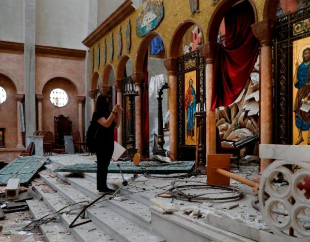 A woman takes pictures ofr a damaged church a day after an explosion hit the seaport of Beirut, Lebanon, Wednesday, Aug. 5, 2020. Residents of Beirut awoke to a scene of utter devastation on Wednesday, a day after a massive explosion at the port sent shock waves across the Lebanese capital, killing at least 100 people and wounding thousands. (AP Photo/Hussein Malla)