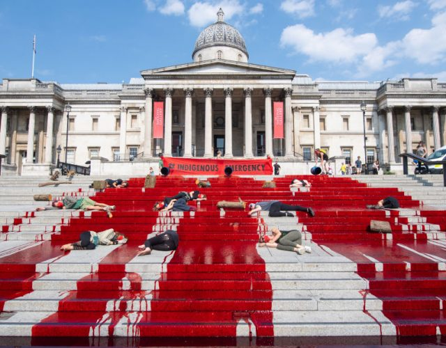 Extinction Rebellion pour dye down the steps near the National Gallery in Trafalgar Square, London, during a protest in solidarity with indigenous communities in Brazil who are dying from Covid-19. (Photo by Dominic Lipinski/PA Images via Getty Images)
