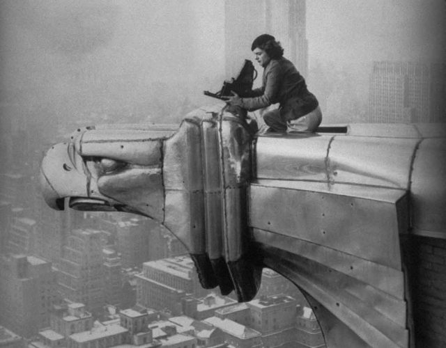 730274: (00/00/1935) LIFE photographer Margaret Bourke-White focusing her camera on a panoramic winter view of the city from a precarious position on an eagle gargoyle atop the Chrysler Bldg.