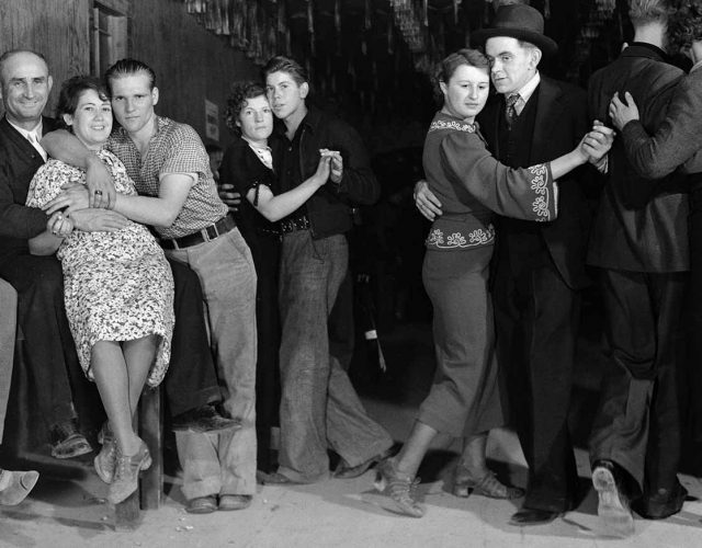 Construction workers and taxi dancers enjoying a night out in bar room in frontier town. LIFE magazine's first photo essay.