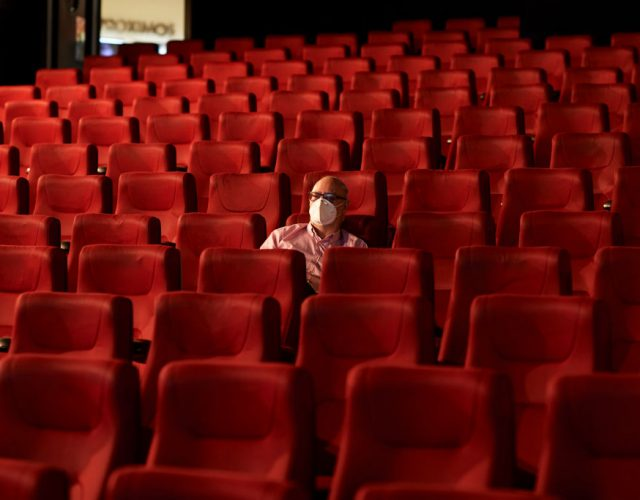 MADRID, SPAIN - JUNE 12: A man wearing a face mask waits for the beginning of the film in the Capitol cinema on June 12, 2020 in Madrid, Spain. The Capitol cinema reopens with a 20% capacity in each of its screening rooms after its closure in the middle of March, because of the Covid-19 pandemic. Spain has largely ended the lockdown it imposed to curb the spread of Covid-19, which caused the death of more than 27,000 people across the country. This week all regions are on Phase One or Two, one month after all of Spain started on Phase zero on May 4, 2020. (Photo by Carlos Alvarez/Getty Images)