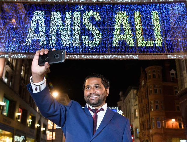 EDITORIAL USE ONLY NHS Volunteer Responder, Anis Ali looks on as his name appears in lights above Oxford Street, London, as the christmas lights are switched on. The lights mark the beginning of the Christmas season in London's West End and this year celebrate the nation's heroes, and for this week, one hero in particular, NHS Volunteer Responder, Anis Ali, as his name lights up the world famous shopping street. PA Photo. Picture date: Monday November 2, 2020. Photo credit should read: Matt Crossick/PA Wire