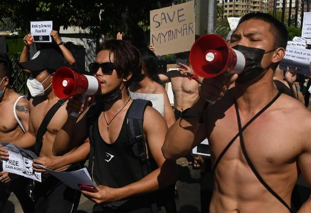 TOPSHOT - Bodybuilders holding signs take part during a protest against the military coup in Yangon on February 11, 2021. (Photo by Sai Aung Main / AFP) (Photo by SAI AUNG MAIN/AFP via Getty Images)