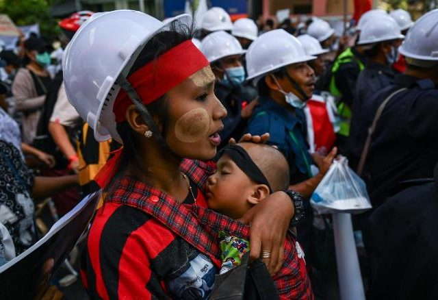TOPSHOT - A protester carries a child march during a demonstration against the February 1 military coup in Yangon on February 10, 2021. (Photo by Ye Aung THU / AFP) (Photo by YE AUNG THU/AFP via Getty Images)