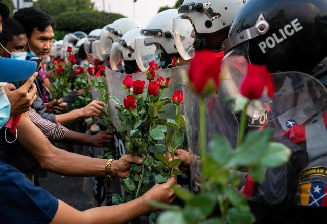 YANGON, MYANMAR - FEBRUARY 06: Protesters give roses to riot police on February 06, 2021 in Yangon, Myanmar. Myanmar's military junta on Saturday placed heavy restrictions on internet connections and suspended more social media services, almost a week after a coup in which it detained de-facto leader Aung San Suu Kyi and charged her with an obscure import-export law violation. Fresh protests broke out on Saturday morning in the country's capital as authorities moved to make mass arrests amid growing civil disobedience. (Photo by Getty Images/Getty Images)